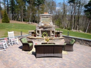 Outdoor living space patio with outdoor fireplace and hearth, retaining wall