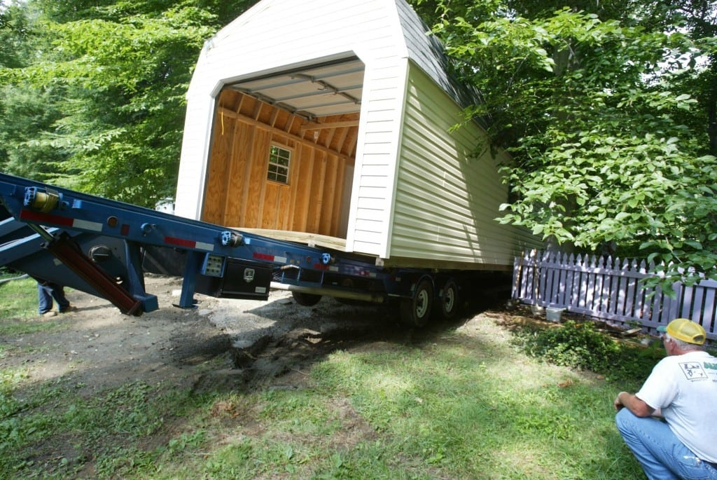 12x24 Storage Barn relocation in Maryland with truck and trailer, storage garage is tucked between fence and trees.