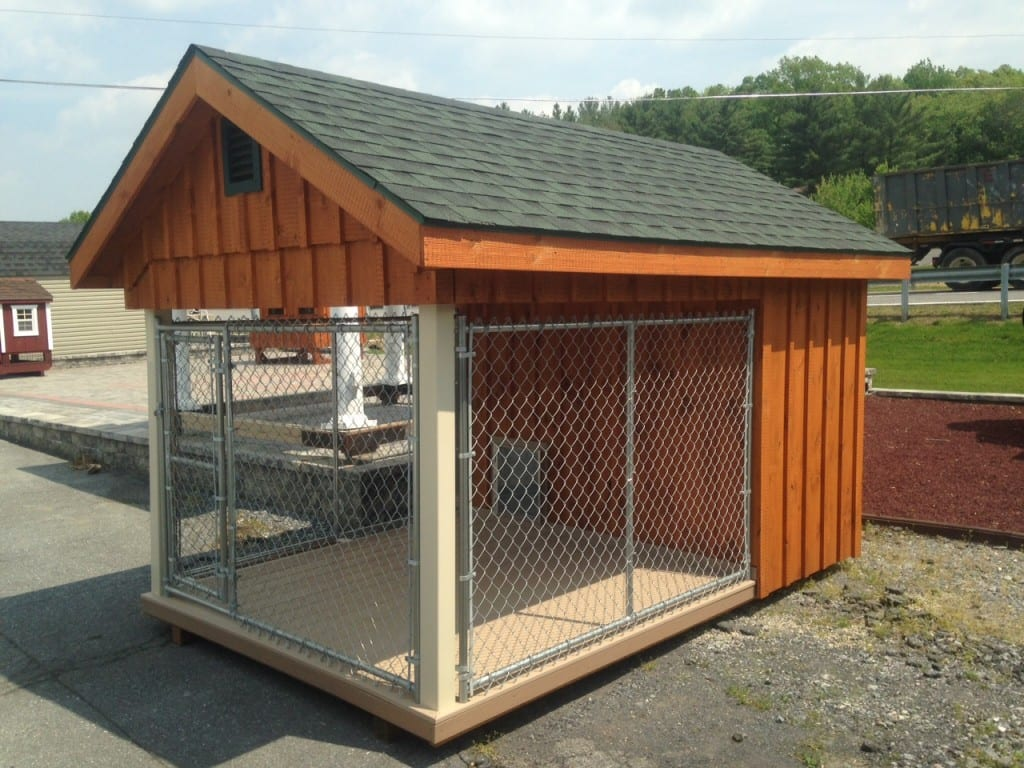 Outside view of dog kennel with vinyl covered posts, shingles, composite decking and dog door entrance.