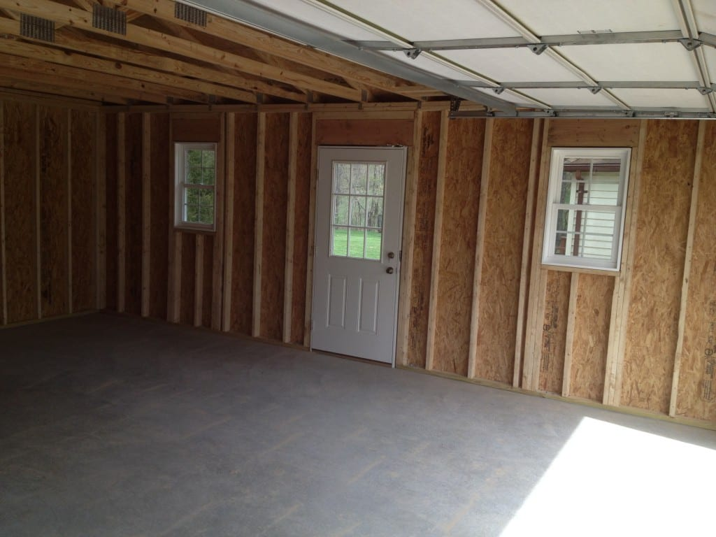 inside of a custom built vinyl garage by 4-outdoor, photo shows inside of garage with concrete pad and side door with two windows on either side of door. concrete was completed by 4-outdoor reviews